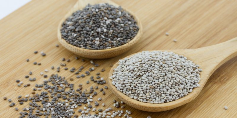 black and white chia seeds on wooden underground